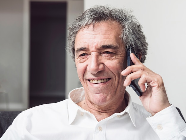 スマートフォンで話す笑顔の上級ビジネスマン 無料写真
