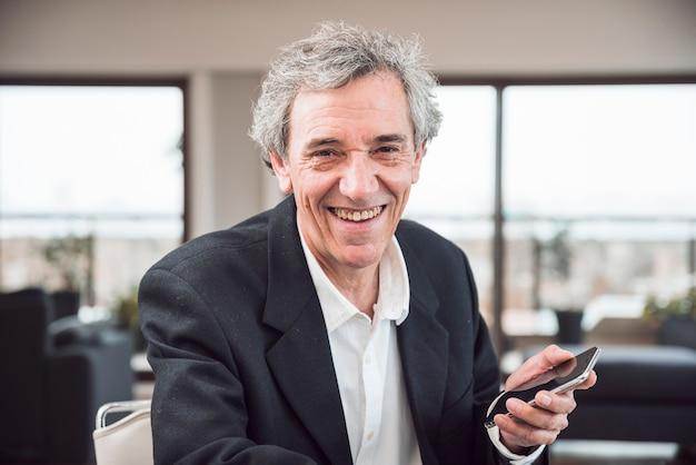 スマートフォンを持っている笑顔の上司の肖像 無料写真