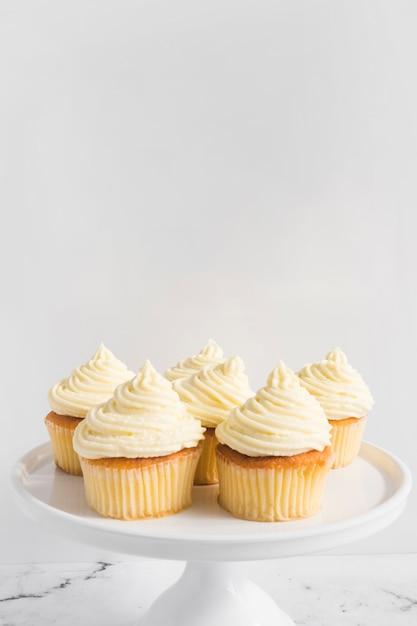 白い背景に対してケーキのスタンドにホイップクリームとカップケーキ 無料写真