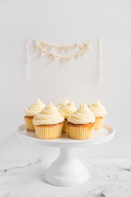 白いケーキのマフィンは白い背景に立つ 無料写真