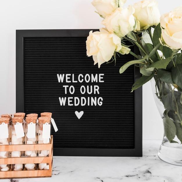 マシュマロテストチューブとバラの花瓶で黒いフレームに結婚式のためのようこそメッセージ 無料写真