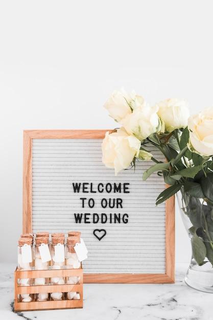 マシュマロテストチューブとバラの花瓶と白いフレームに結婚式のためのようこそメッセージ 無料写真