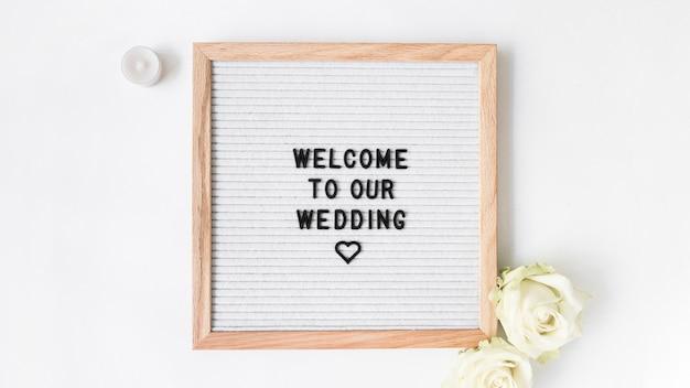 キャンドルと白い背景で結婚式のためのウェルカムフレームとローズ 無料写真