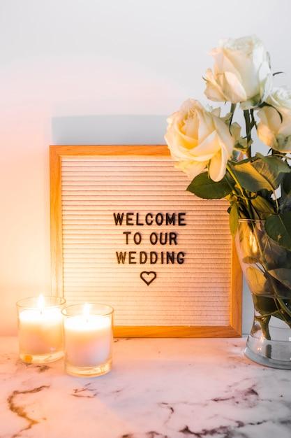 結婚式のウェルカムボードと白い背景の花瓶の近くに点灯したろうそく 無料写真