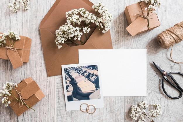Детские цветы в конверте с пустой бумагой; обручальные кольца; катушка и поляроидная рама Бесплатные Фотографии