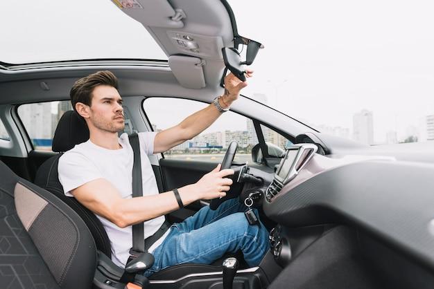 リアビューミラーを調整している若者運転車 無料写真