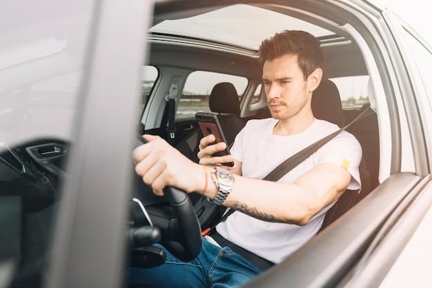 スマートフォンを使用して車を運転している若者 無料写真
