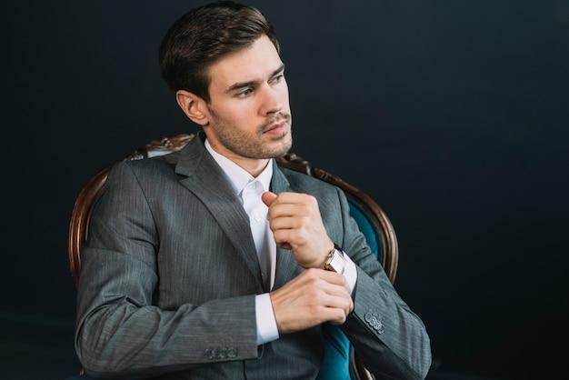 魅力的なハンサムな若い男は、黒の背景にヴィンテージチェアに座って 無料写真
