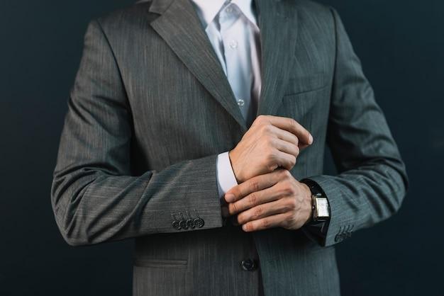 彼の袖を調整するスーツの若い男の中央部 無料写真