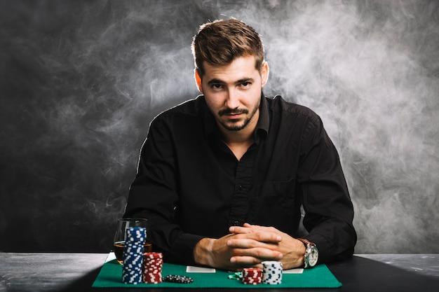 カジノのチップとトランプを持つ男性プレーヤーの肖像 無料写真