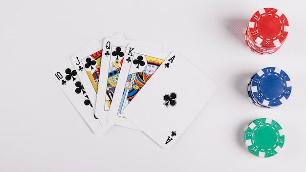 白い背景にロイヤルフラッシュクラブとカジノチップでプレーするカード 無料写真