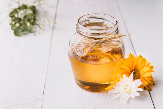 木製の背景に白と黄色の花と蜂蜜の瓶 無料写真
