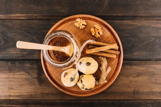 蜂蜜の高台;クルミ;木製の背景にスパイスとカップケーキ 無料写真