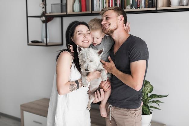 彼らのかわいい息子と白い犬と家で愛する若いカップル 無料写真