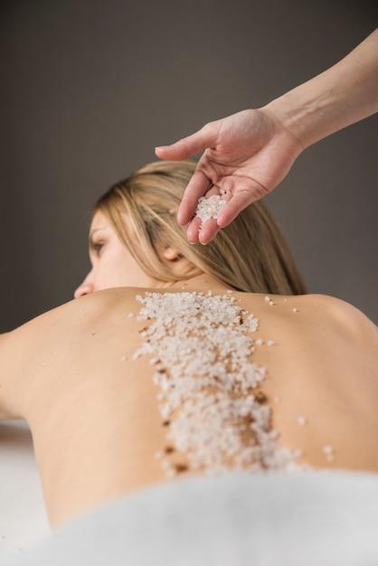 女性、背中に塩を塗るセラピストの手のクローズアップ 無料写真