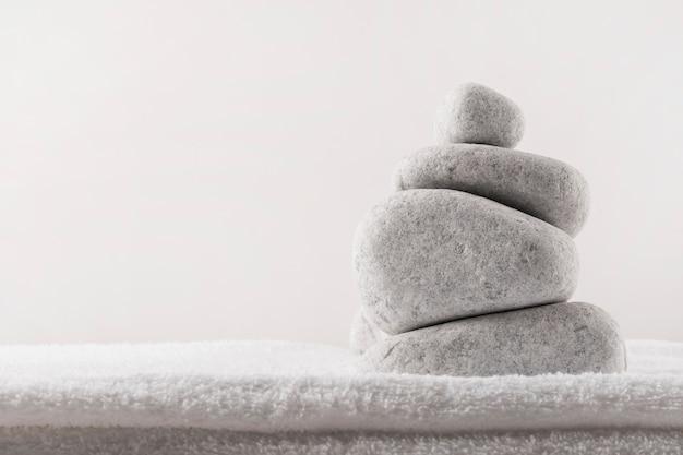 柔らかい折り畳まれたタオルの上に白い背景のスパ石のスタック 無料写真