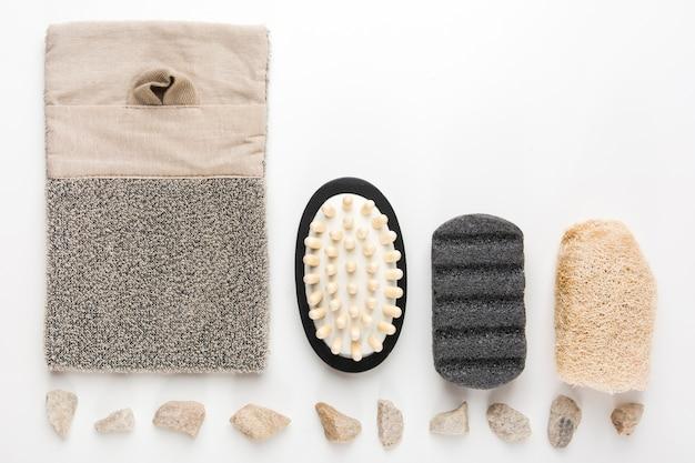 スーフールと並んで配置されたスパルーム。マッサージブラシ;スクラバー;白い背景に軽石 無料写真