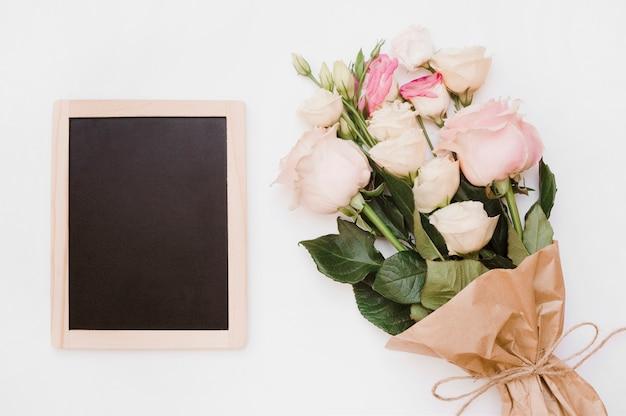 白い背景に花の花束と小さな空白の木製のスレート 無料写真