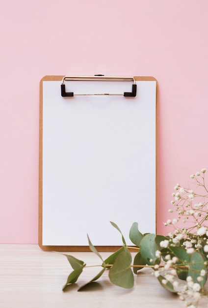 ピンクの背景に木製の机の上に葉と赤ちゃんの息の花とクリップボードに空白の白い紙 無料写真