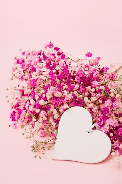 ピンクの背景に赤ちゃんの呼吸の花と空白の白いハート型 無料写真