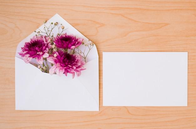 花と木製のテクスチャの背景にカードと白い封筒 無料写真