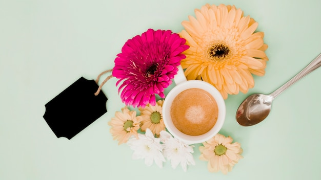 色とりどりの背景に花の装飾と黒の空白のタグが付いているコーヒーカップのオーバーヘッドビュー 無料写真