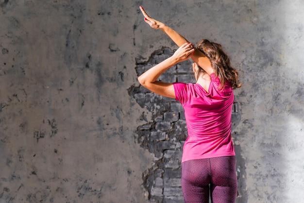 彼女の腕を伸ばしている壁の前に立っている女性のクローズアップ 無料写真