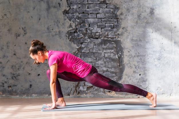 ストレッチ練習をしているスポーツウェアで美しい若い女性の側面図 無料写真