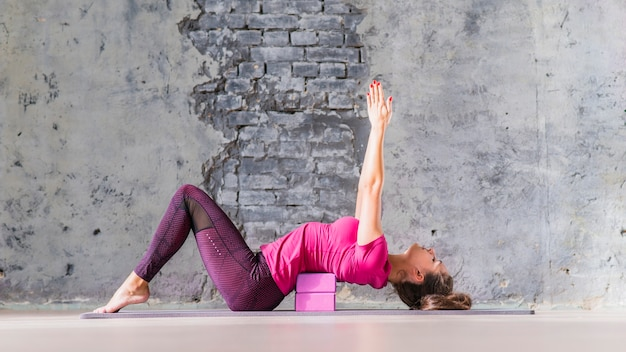 ピンクのブロックを使用してヨガを練習している若い魅力的なスポーティなヨーヨーの女性 無料写真