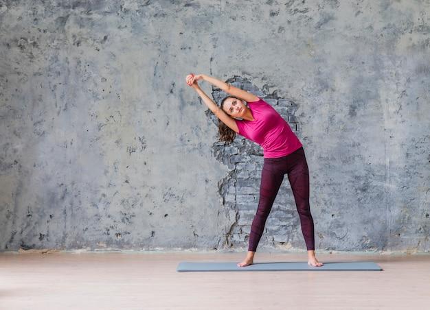 灰色の壁に向かってフィットネス運動をしているスポーティな若い女性 無料写真