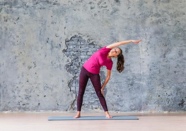 ヨガのクラスでストレッチ運動をしている若い女性 無料写真