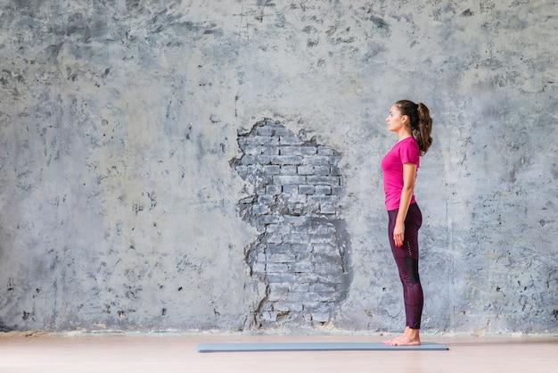 グレーの風化した壁の上に運動マットに立っている若い女性の側面図 無料写真