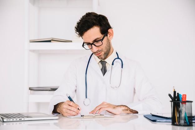 病院でクリップボードに書いている男性医者 無料写真