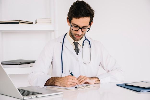 クリニックのクリップボードに書いている医者の肖像 無料写真