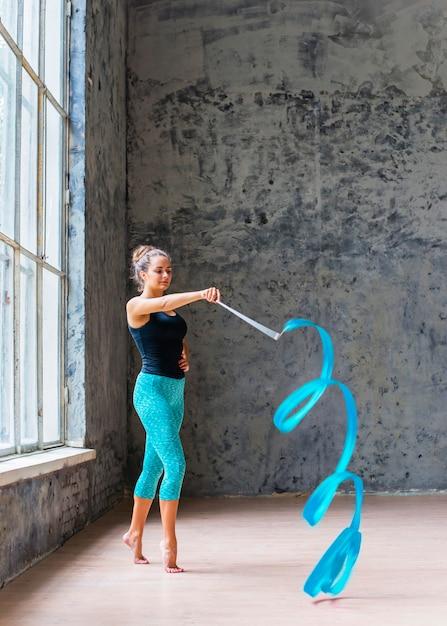 青いリボンで踊っている美しいダンサー 無料写真