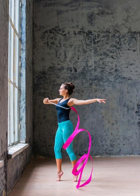美しい若い女性がピンクリボンで踊っているの側面図 無料写真