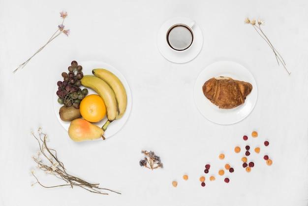 クロワッサンとフルーツの白いプレートにコーヒーとドライフラワーの白い背景の上 無料写真