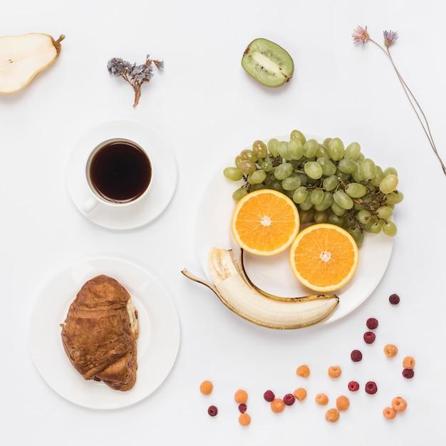 白い皿の上の果物とコーヒーで作られたスマイリーフェイス。クロワッサンとコーヒーの白い背景で隔離 無料写真