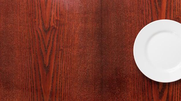木製の織り目加工の背景に空の白いプレート 無料写真