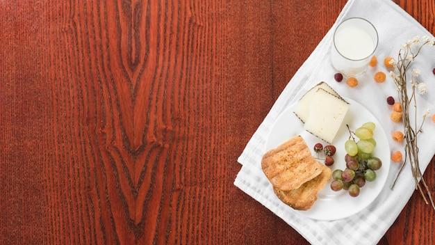 コップ一杯分の牛乳;パン;ケーキのスライスぶどうイチゴとラズベリーの木製テーブルの上の白いナプキン 無料写真