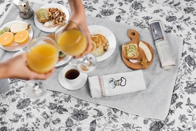 Вид сверху двух человек, поджаривающих стакан сока за завтраком Бесплатные Фотографии