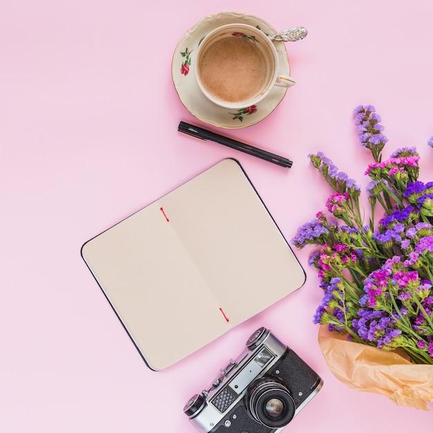 Возвышенный вид букета цветов; винтажная камера; дневник; ручка и чашка кофе на розовом фоне Бесплатные Фотографии