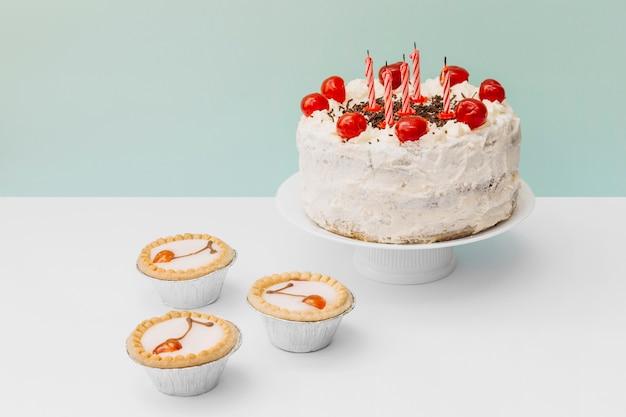 ミニのタルトとケーキの上に飾られたケーキは二重の背景に立つ 無料写真
