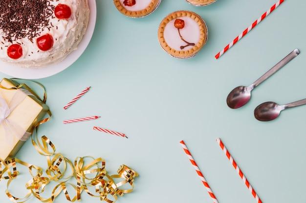 誕生日ケーキ;タルト;ストロースプーン;ろうそくギフト用の箱と青い背景上ののぼり 無料写真