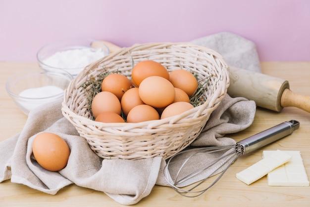 Корзина полна цельных яиц; мучной; сахар; белый шоколад; веники и скалку на деревянный стол Бесплатные Фотографии