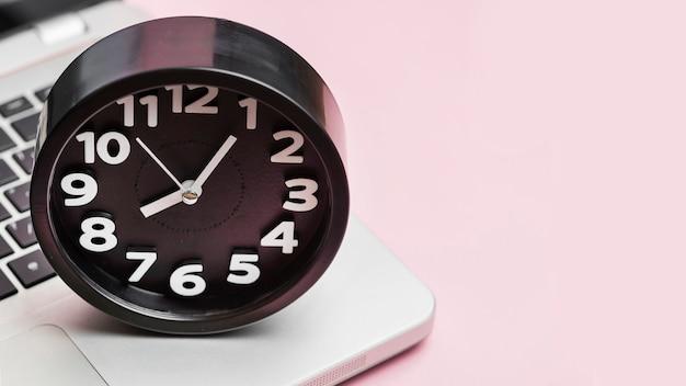ピンクの背景のラップトップ上の目覚まし時計 無料写真