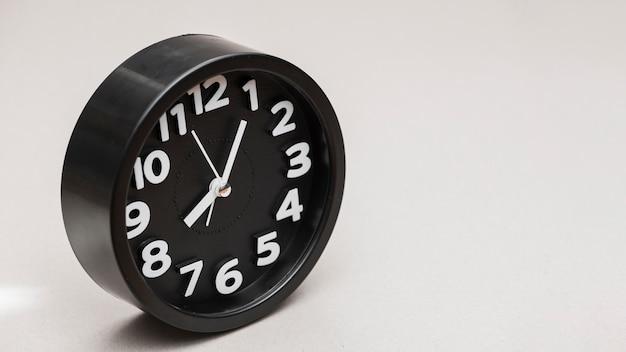 灰色の背景に対して円形の黒い目覚まし時計 無料写真