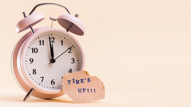 ベージュ色の背景に対して目覚まし時計の近く引き裂かれた紙の上のテキストをタイムズします。 無料写真