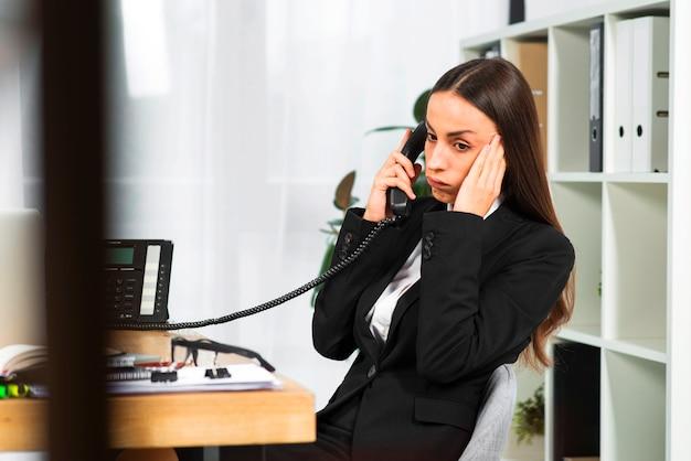 電話で聞いて木製の机のそばに座って心配している若い実業家 無料写真