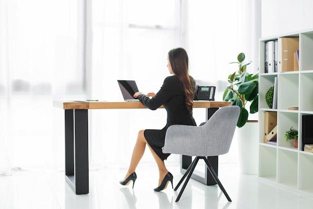 オフィスでラップトップを使用して実業家の側面図 無料写真